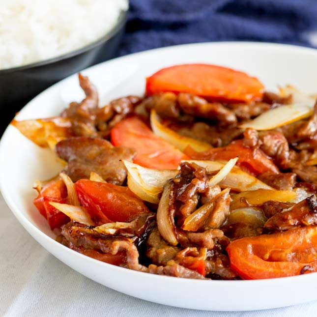 square image of a white bowl cantonese style beef and tomatoes