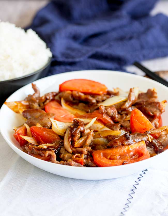 table view of a white bowl of beef stir fry with tomatoes, a bowl of rice in the back ground with a blue napkin and black chopsticks