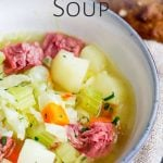 close up of the corned beef soup in a blue bowl with text at the top