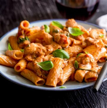 a pale blue plate with rigatoni pasta in a cream tomato sauce garnished with basil