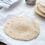 homemade flour tortilla on a sheet of baking paper