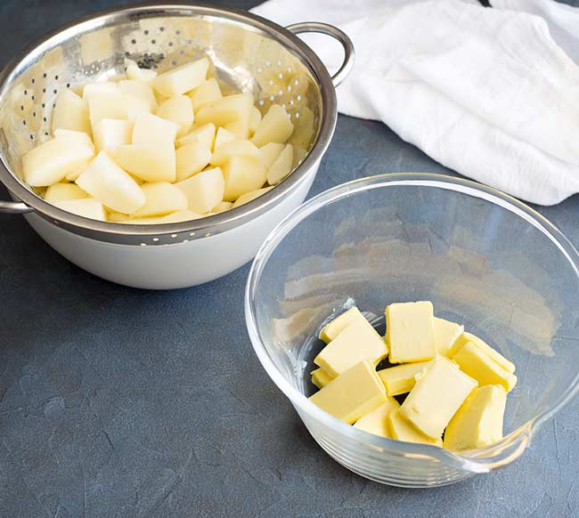 a bowl of cooked potatoes and a bowl of chopped butter