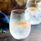 two G&T's in stemless whine glasses garnished with ornage zest and a thyme sprig