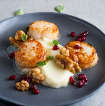 square picture of 3 seared scallops with cauliflower puree on a grey plate garnished with walnuts, pomegranate and herbs