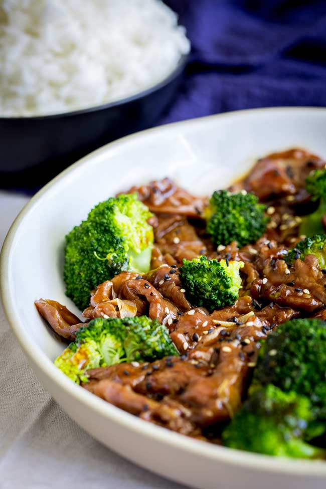 Close up on the white bowl with the beef and broccoli in it, with rice in the background