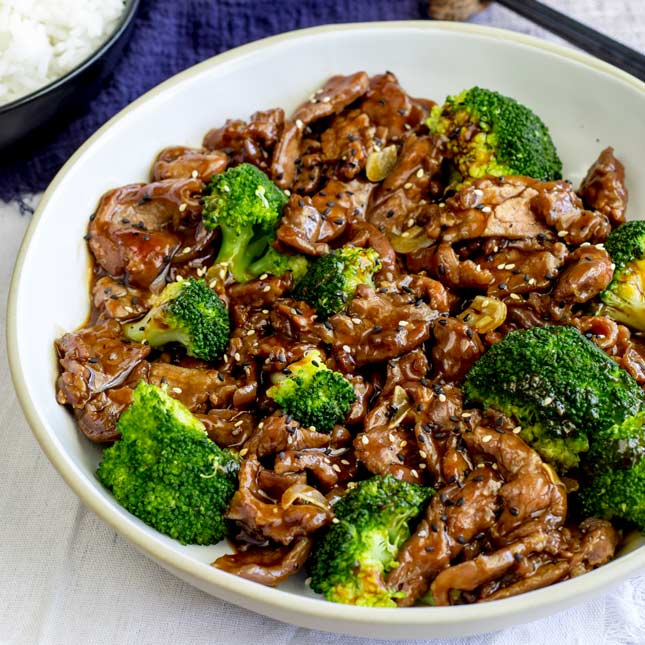 square picture from overhead showing the beef and broccoli in a large white bowl with a blue napkin, bowl of rice and chopsticks