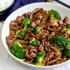 Beef and broccoli takeout style in a white bowl