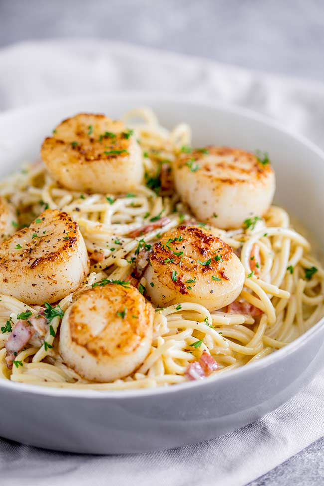 overhead view showing 6 seared scallops sat on a bowl of spaghetti