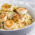 a shallow grey bowl of spaghetti with seared scallops on top