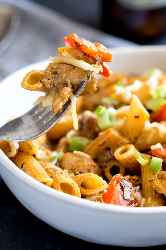 a silver fork picking up some cajun chicken pasta from a white bowl