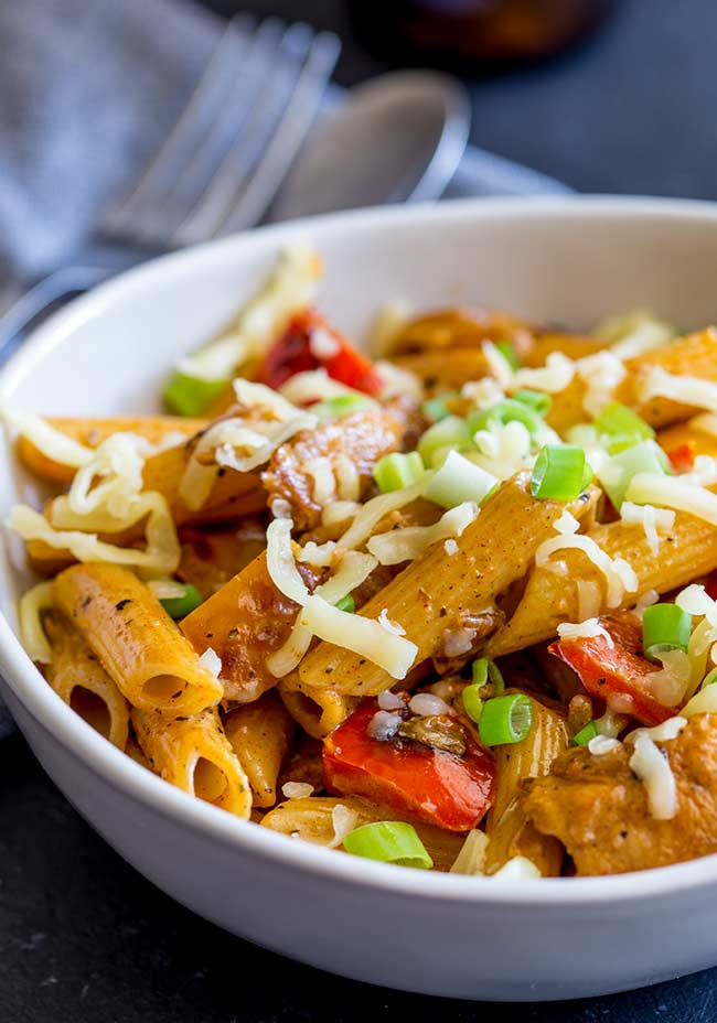 a white bowl filled with cajun chicken and sausage pasta