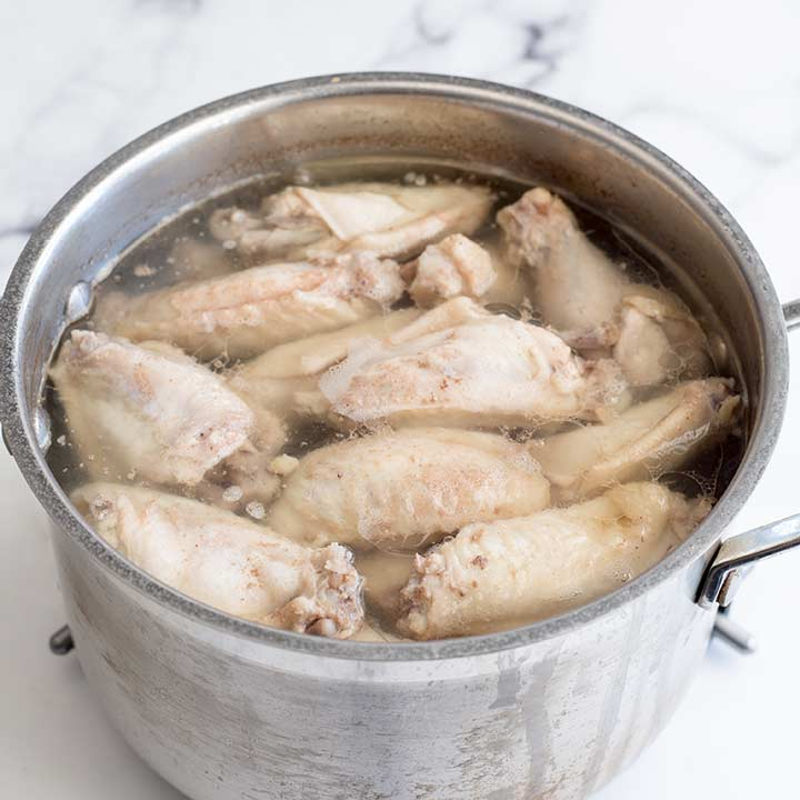 silver pan of water with poached chicken wings in it