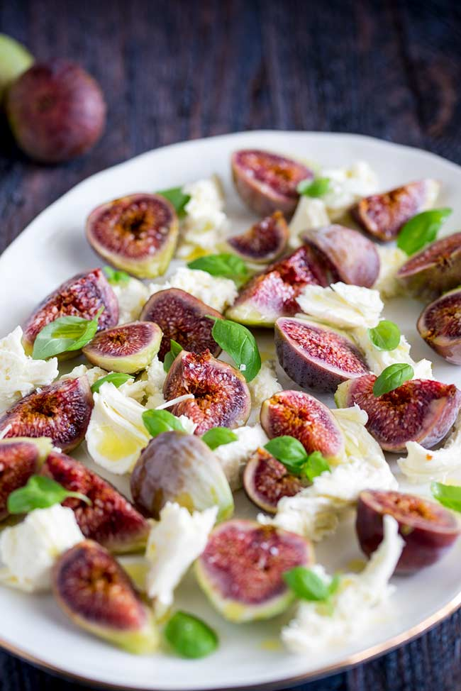 a white platter of quartered figs and fresh mozzarella