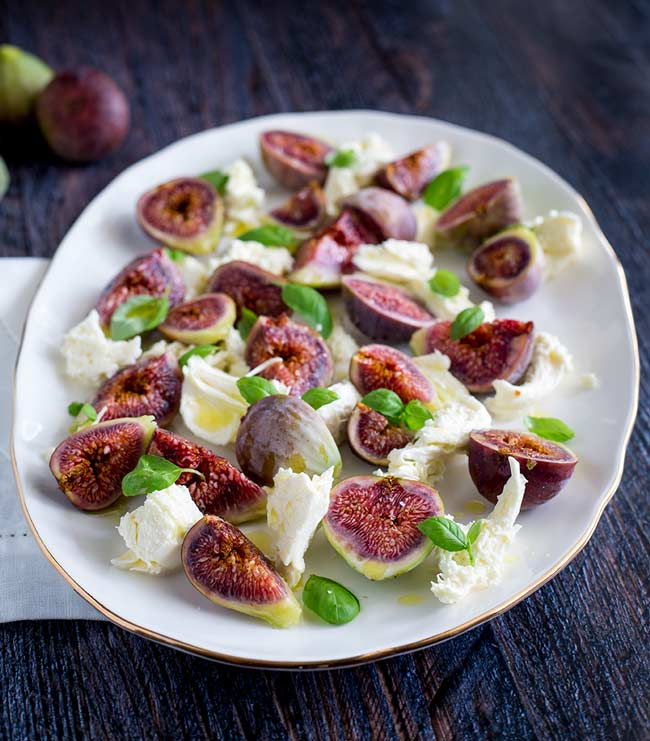 over the head view of a platter of fig caprese on a wooden table