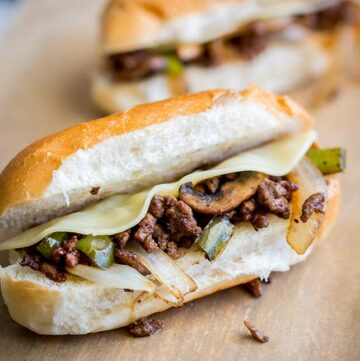 Square picture showing a close up of the ground beef cheesesteak on brown paper and a wooden board