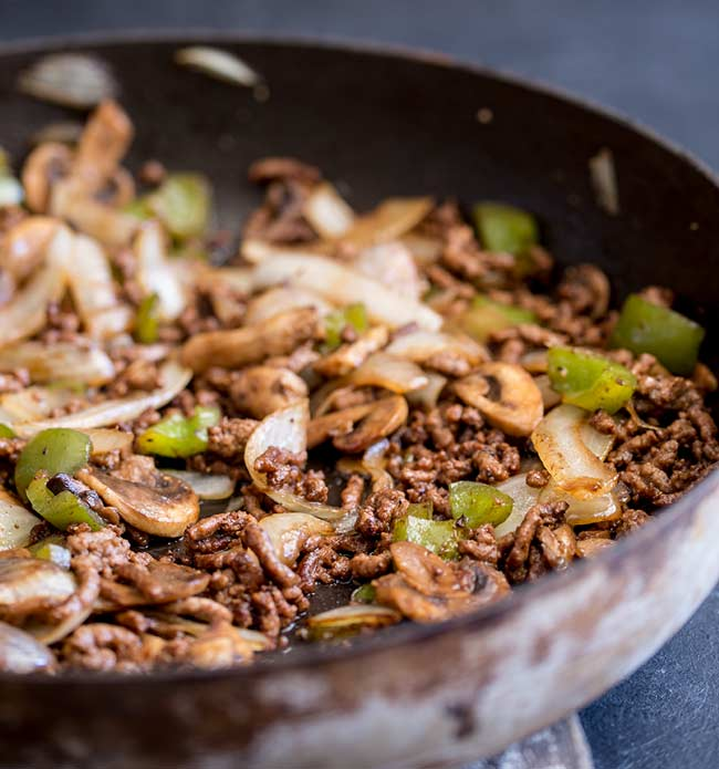 large skillet full of cooked ground beef, onion, pepper and mushroom
