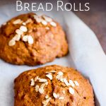 close up on two brown Guinness bread rolls sprinkled with oats