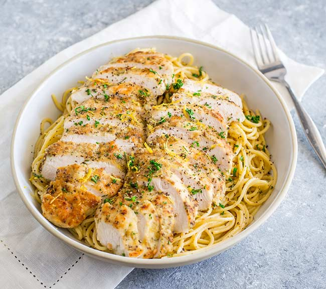 overhead showing sliced lemon pepper chicken breasts on a bed of pasta