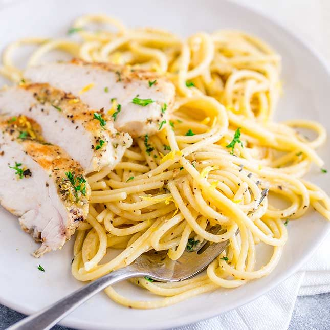overhead of a white plate with lemon pasta in it and a silver fork