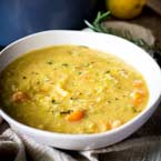 close up on a rustic bowl of yellow soup garnished with lemon and rosemary