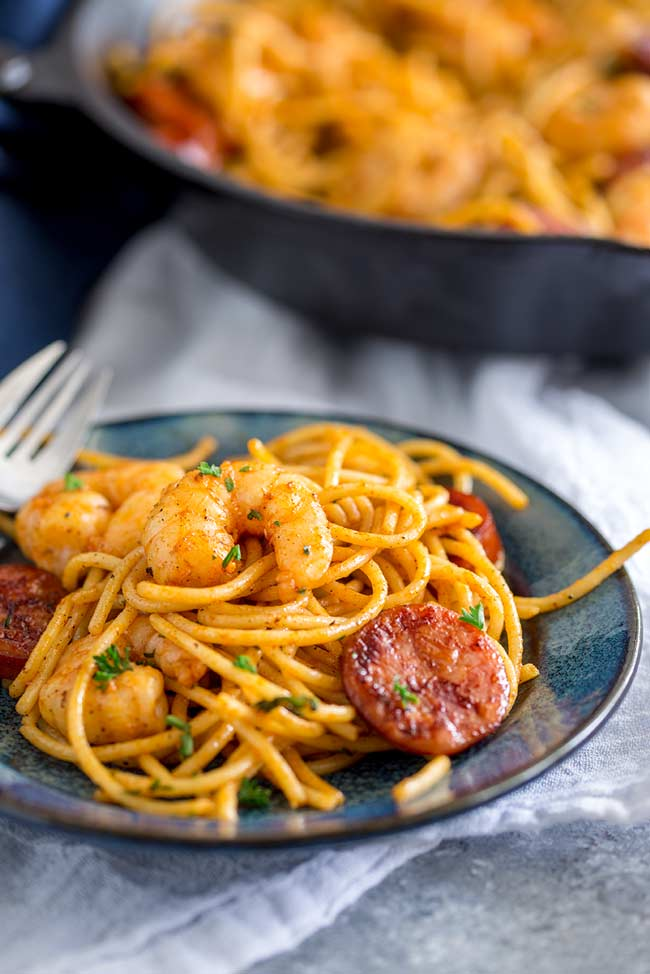 a close up on the paprika tinged shrimp chorizo pasta on a blue plate with a fork in the background