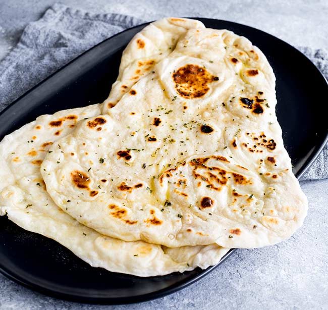 overhead view showing two garlic naan breads on a black plate