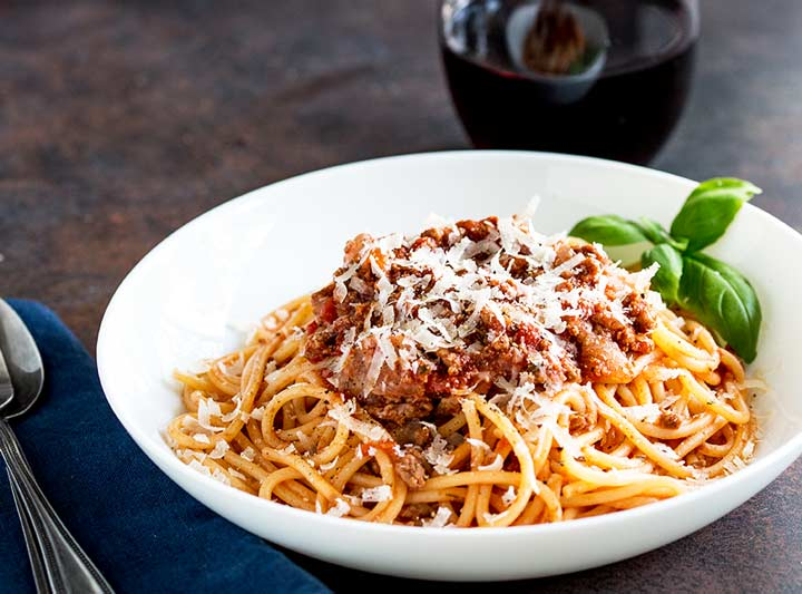 A shallow white bowl filled with spaghetti bolognese garnished with parmesan and basil
