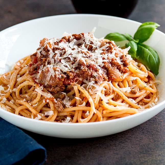 a white bowl of spaghetti bolognese on a dark table with a blue napkin