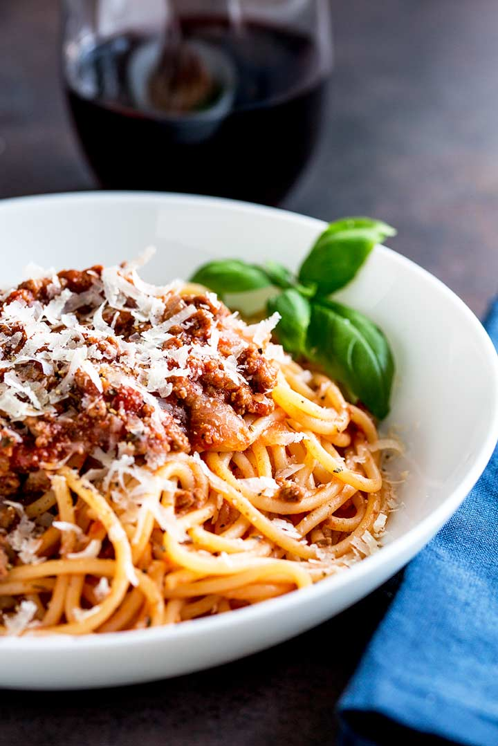 spaghetti bolognese in a white bowl on a dark table, garnished with basil