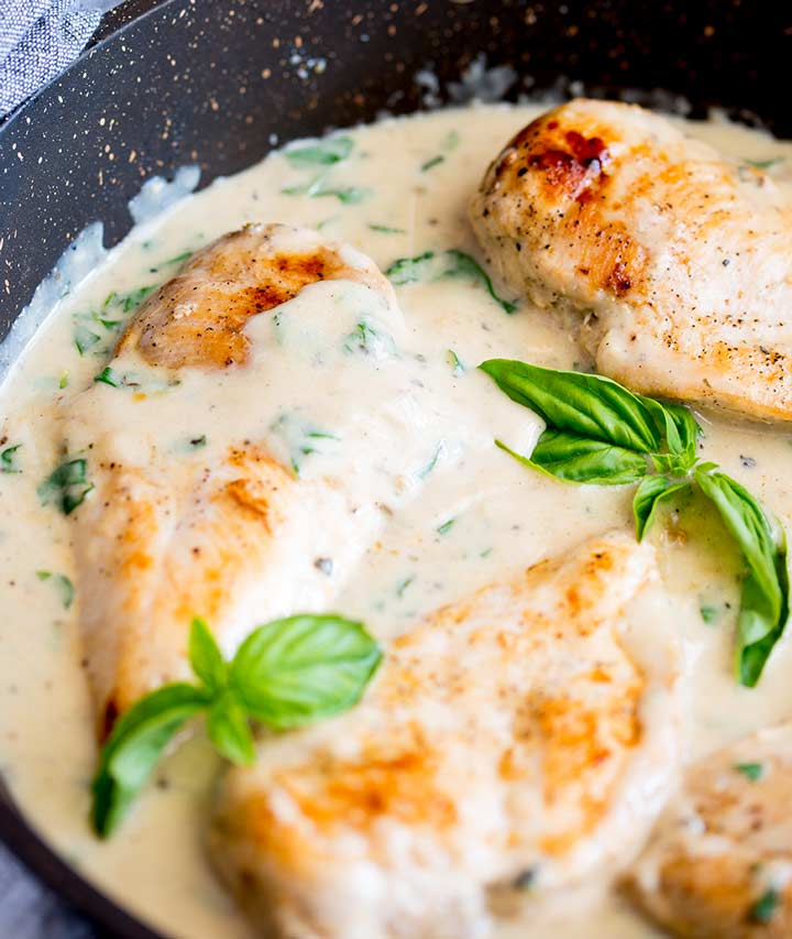 close up on the creamy basil sauce in a black skillet
