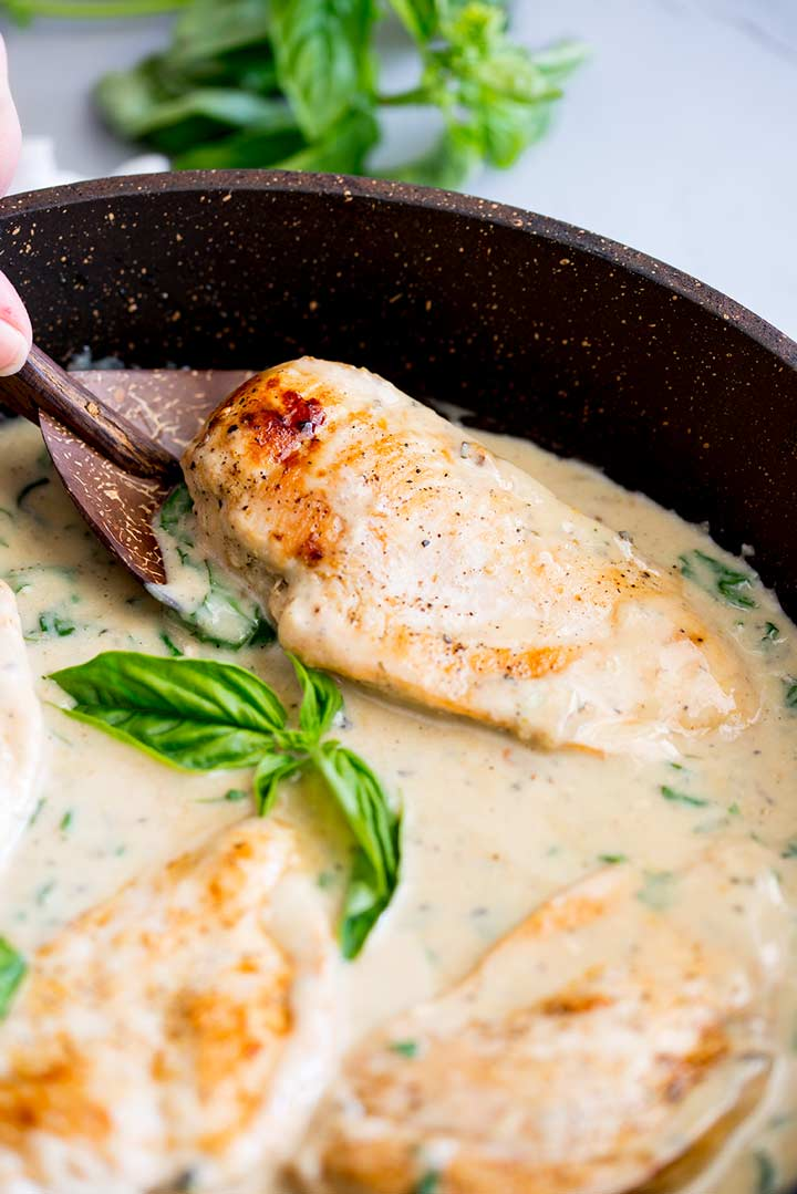 a wooden spoon scooping out a chicken breast from a black pan of basil cream sauce