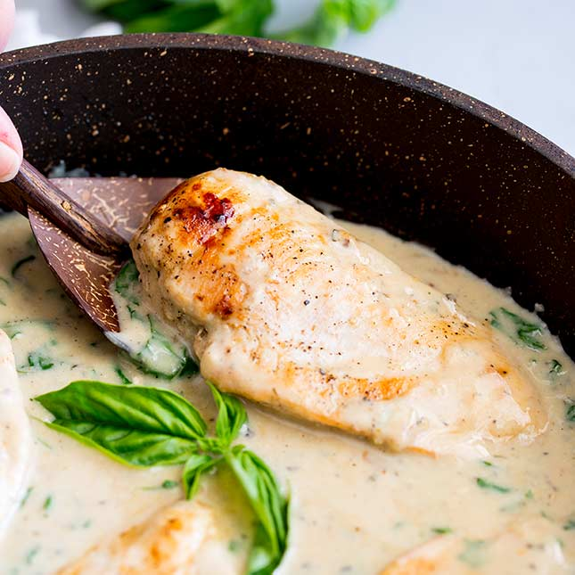 a flat brown spoons scooping up a chicken breast from a pan of sauce