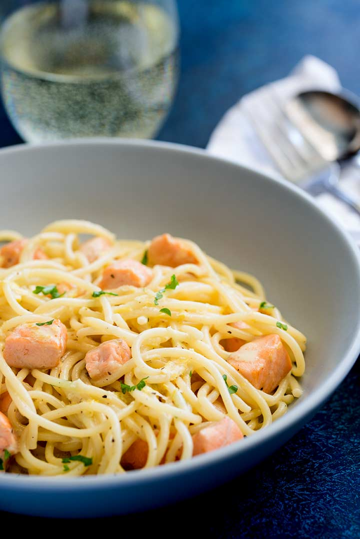 a grey bowl of spaghetti and salmon on a blue table