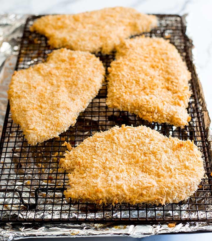 4 chicken schnitzels on a baking rack