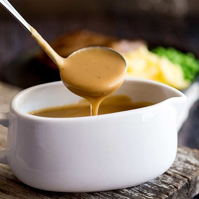 close up on a ladle of gravy pouring into a white gravy boat