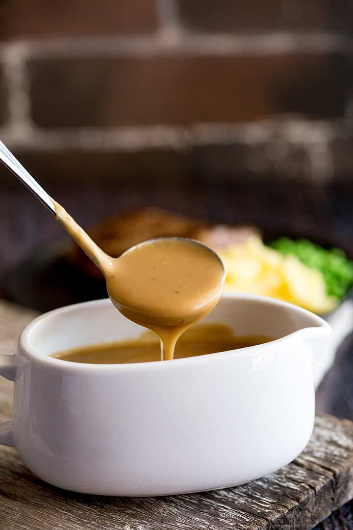 a small ladle scooping some brown gravy out of a white gravy boat