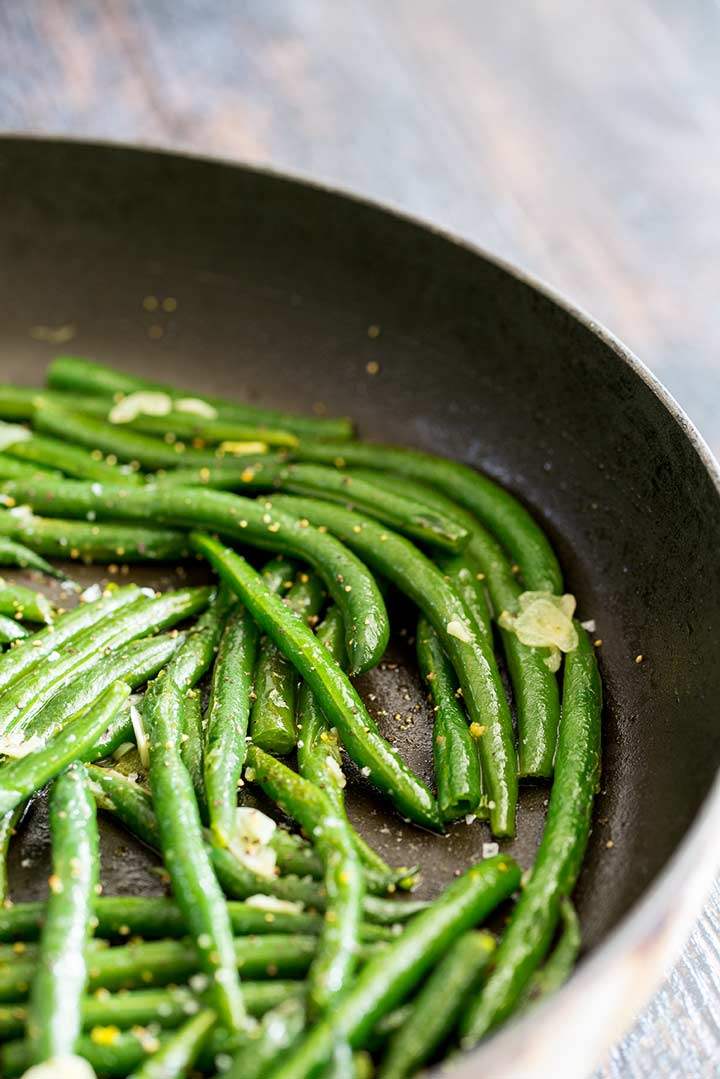 green beans and sliced garlic in a black skillet