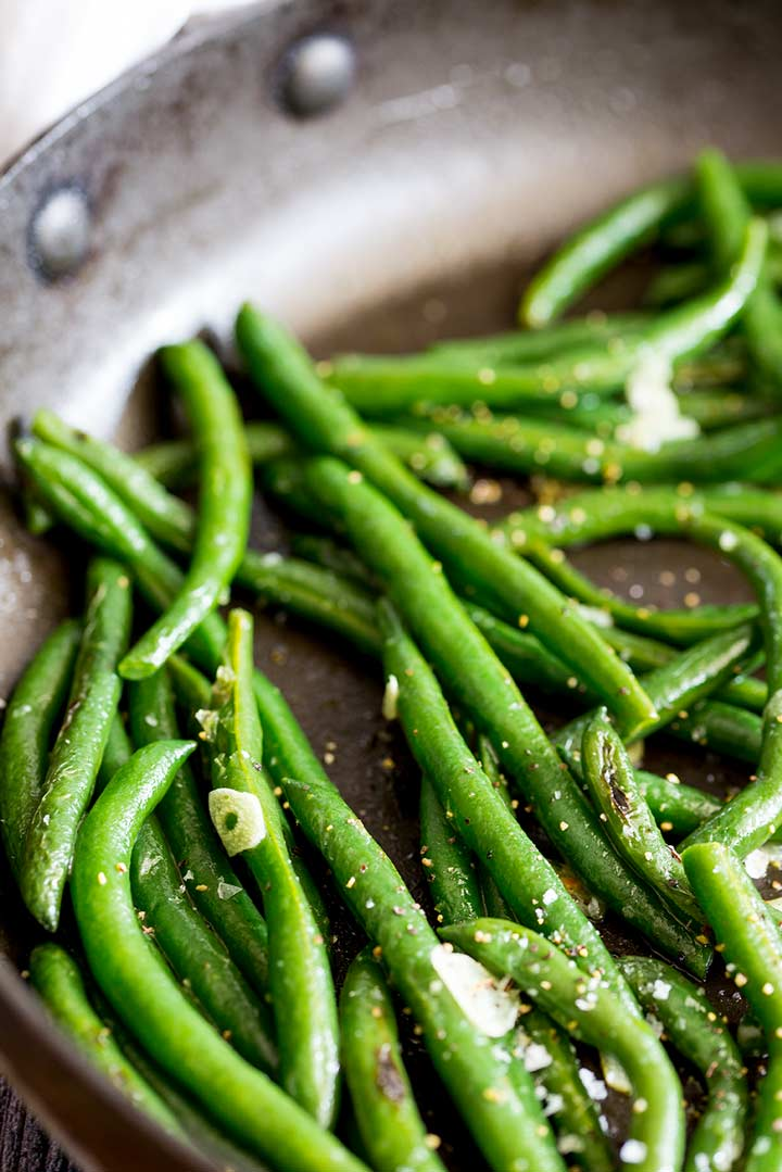 sautéed green beans in a black skillet