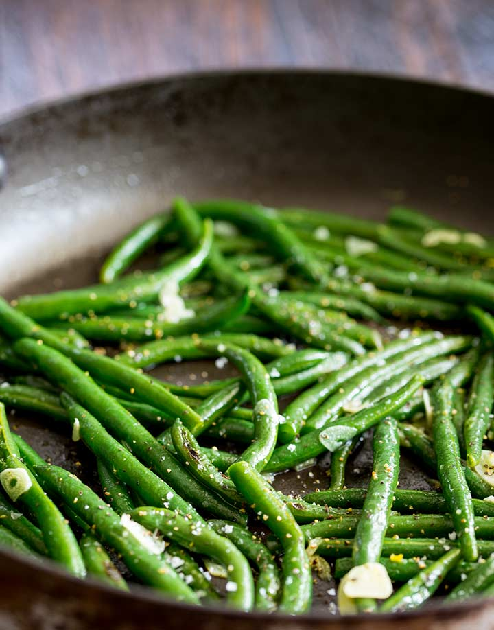 Close up on the seasoning on the green beans in a black skillet
