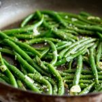 overhead view of a large black skillet with green beans and garlic