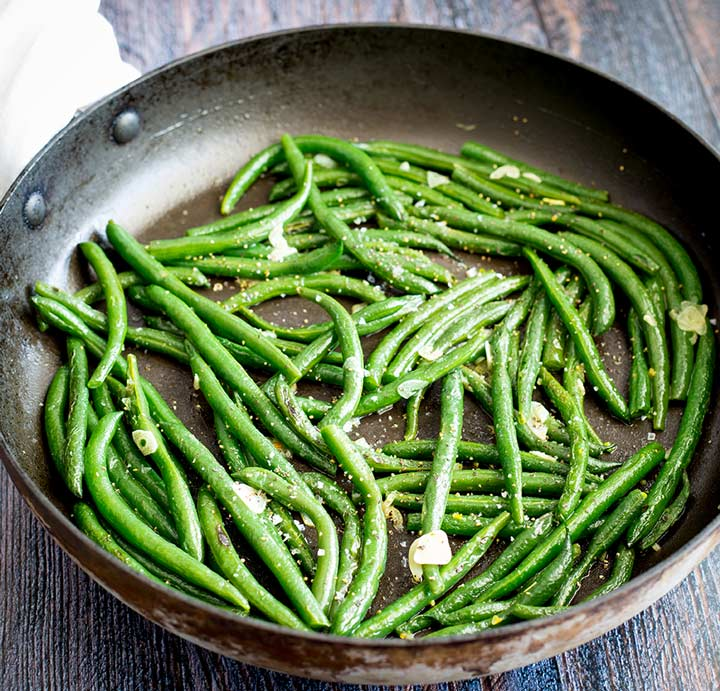 a skillet of green beans on a wooden table
