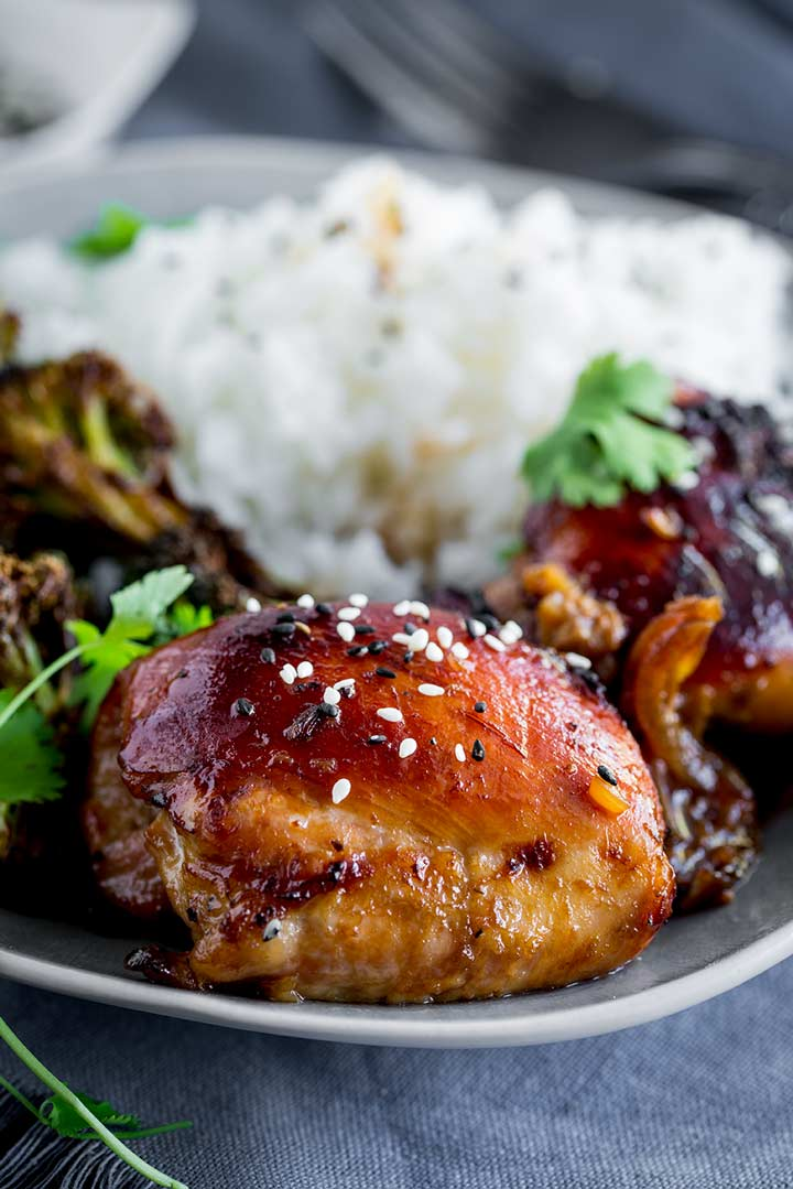 close up on a chicken thigh garnished with sesame seeds with rice in the background.
