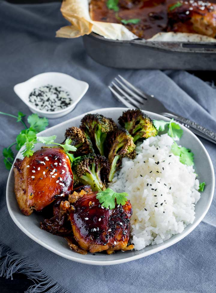 a grey plate with honey soy chicken, rice and roasted broccoli on it