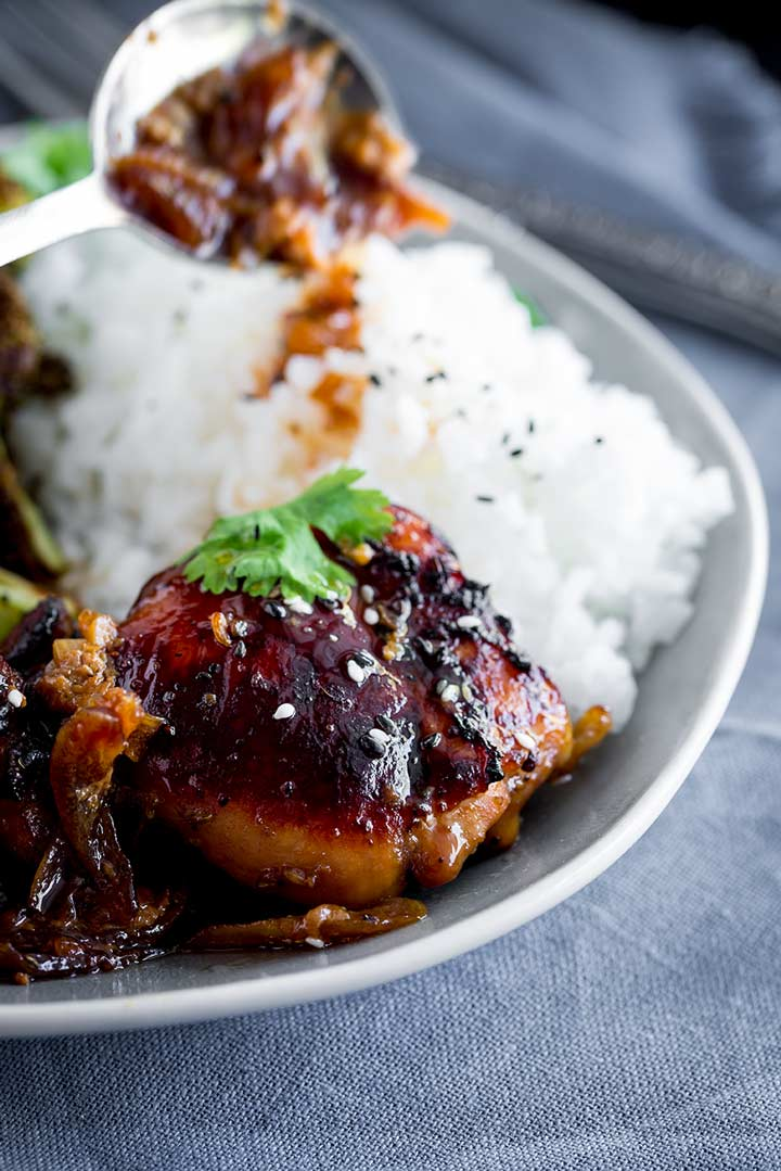 sticky chicken thigh garnished with cilantro and sesame seeds