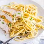 white plate with lemon pepper spaghetti and some slices of chicken