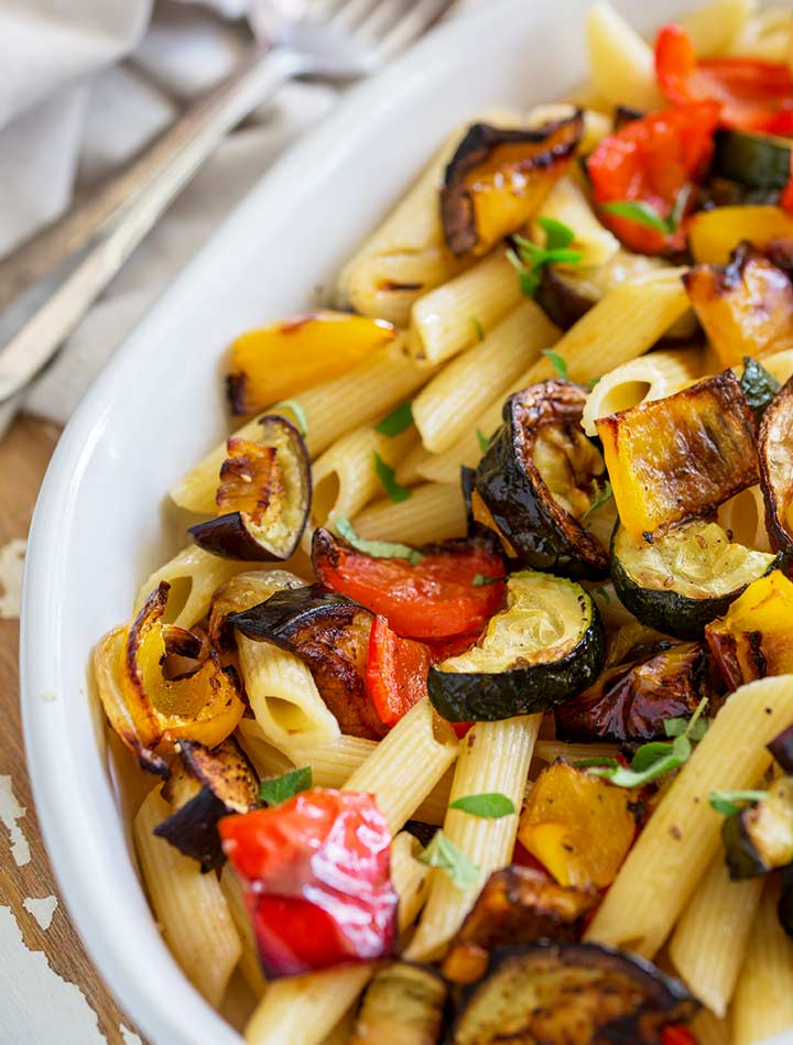 close up on the roasted vegetables in a white oval dish of pasta