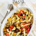 overhead view of a dish of Mediterranean Roasted Vegetable Pasta on a worn white table with text at the top