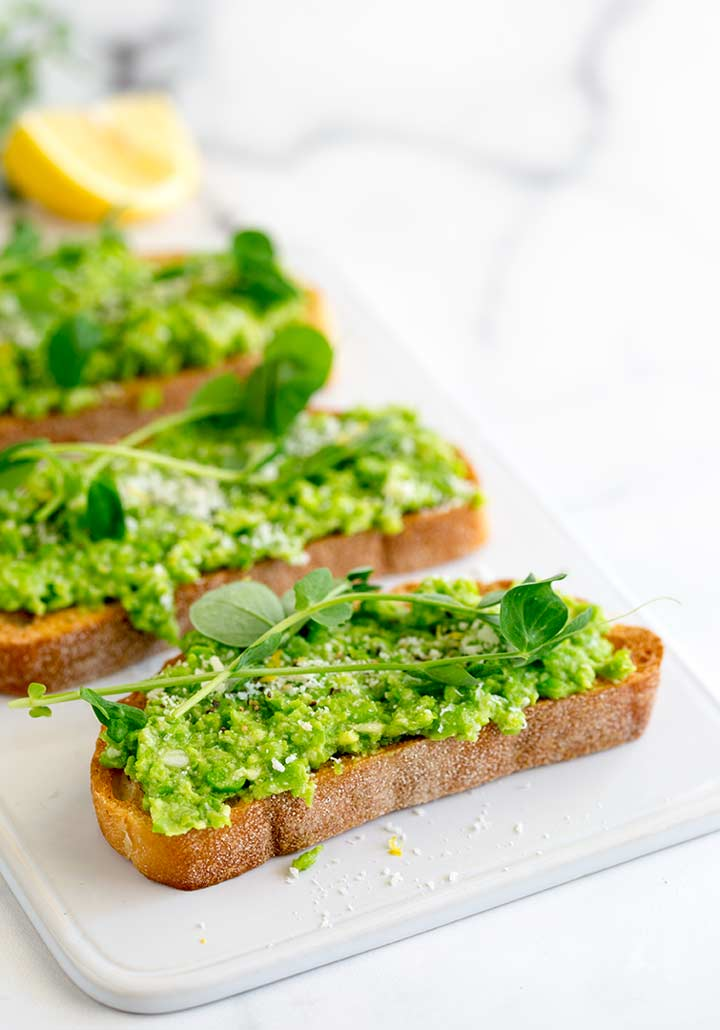 a slice of toast with pea pesto on it garnished with lemon, parmesan and pea shoots