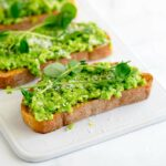 a white tray style plate with a pea bruschetta on it