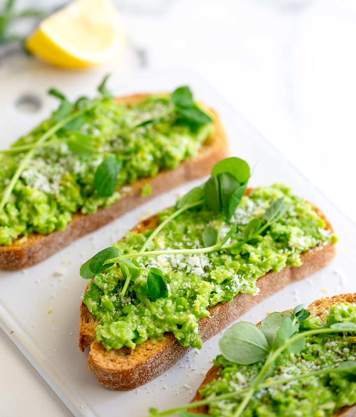 overhead shot of pea bruschetta on a flat white plate with lemon and pea shoots in the background